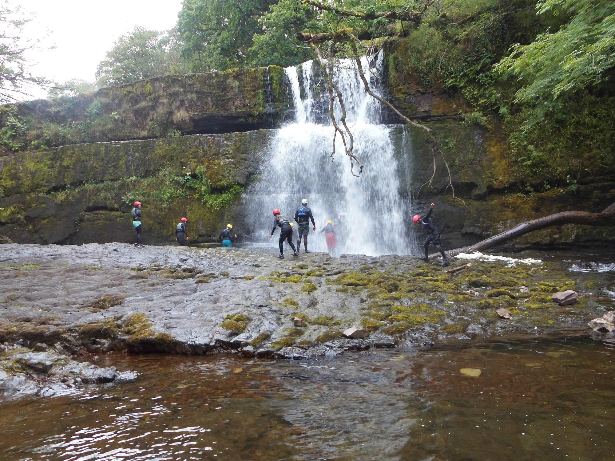 Walking past a large waterfall whilst gorge scrambling