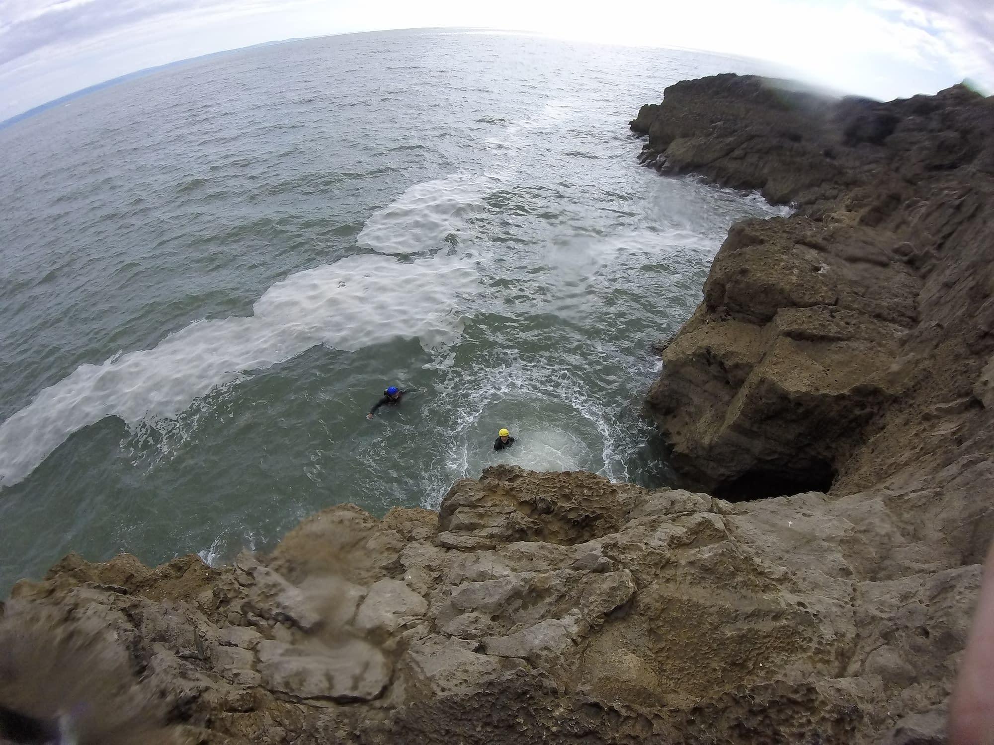 People swimming in sea after big coasteering jump
