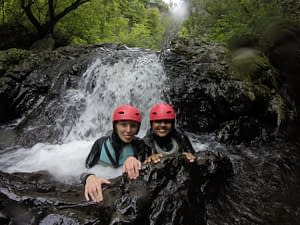 Two ladies in front of a waterfall whilst gorge walking in near Cardiff, South Wales