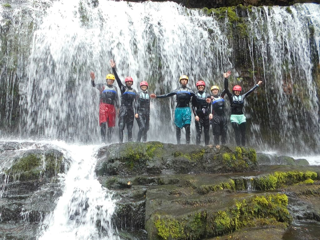 Group of guys in front of a waterfall whilst gorge scrambling near Cardiff, South Wales