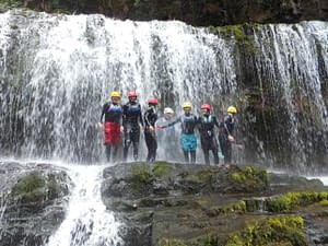 Group standing on a cliff under a waterfall whilst gorge scrambling