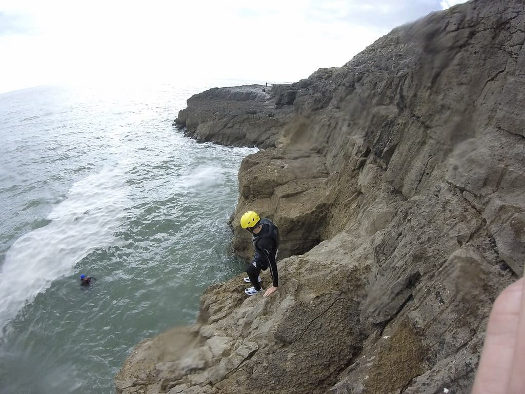 Traversing a cliff in South Wales during Coasteering activity